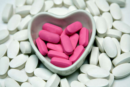 A heart shaped dish filled and surrounded by pills.
