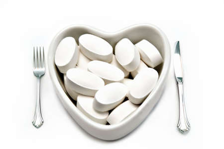 A hearth health concept - isolated on white - heart shaped plate full of medicine, knife and fork. Stock Photo - 898822