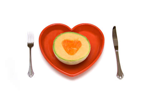 Health concept - half of a cantaloupe on a heart shaped plate - isolated on white.  Stock Photo