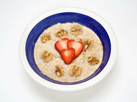 Heart and health concept.  Strawberries, walnuts top a bowl of oatmeal.  photo
