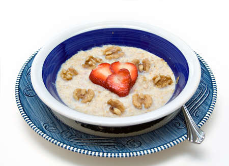 Health concept - oatmeal, walnuts and heart-shaped strawberry slices.  photo