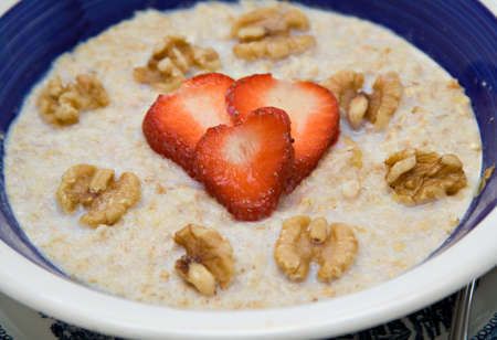 Heart Health concept - strawberries in heart shape on bowl of oatmeal withwalnuts.  photo