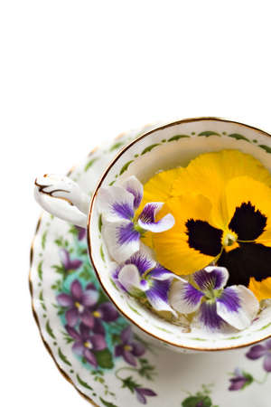 Teacup with pansies and violiets on white background - shallow depth of field.