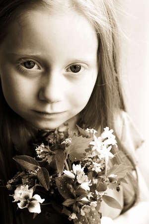 A small girl with long hair holding a bouquet of flowers