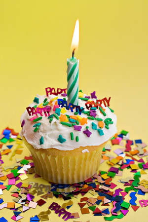 A party cupcake with flaming candle on yellow background.