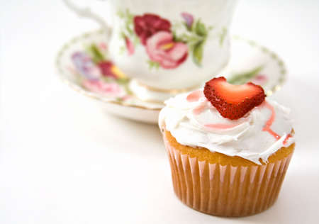 sweetest: A yellow cupcake decorated with frosting and a heart-shaped strawberry slice. Teacup in background - shallow depth of field.