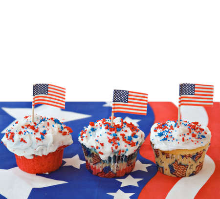 Three American themed cupcakes topped with flags.  photo