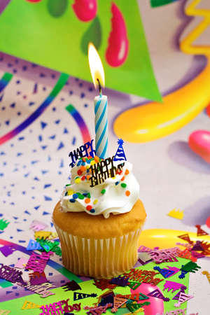 Birthday Party Cupcake with bright colorful background.  Blue lit candle sprinkles and confetti.