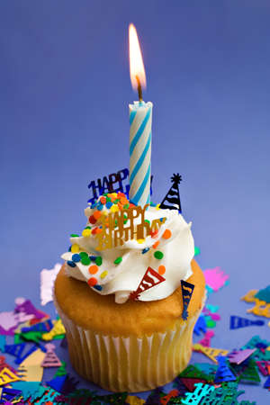 A blue birthday theme party cupcake with lit candle.  Stock Photo