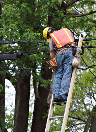 electric utility: A worker on ladder repairing the lines.