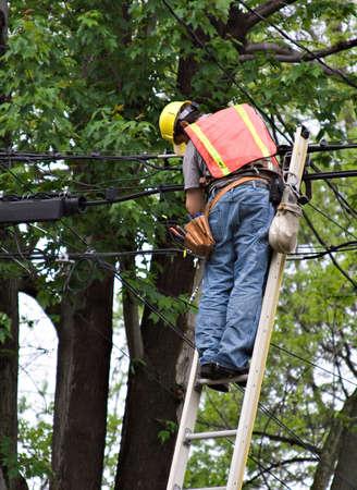 blackout: Een werknemer op de ladder het repareren van de lijnen. Stockfoto