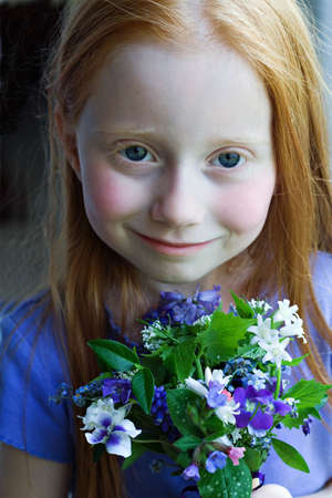 A small red-haired girl holding a small bouquet of spring flowers.  Soft focus.