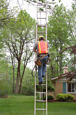 outage: A worker in yellow hardhat climbs a ladder to repair a line above. Stock Photo