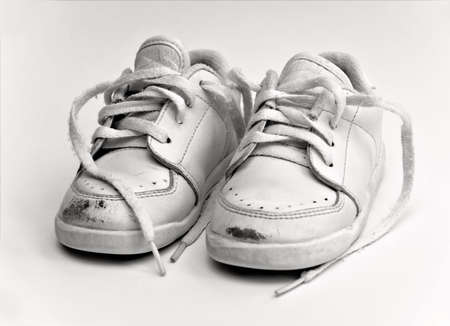 scuff: An old worn pair of white  -  toddler shoes. Stock Photo