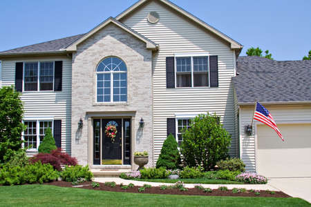 suburban home: A beautiful neat suburban home in Ohio flying the American Flag. Stock Photo