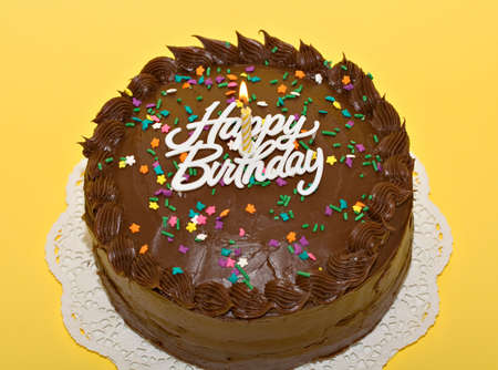 sweetest: Chocolate birthday cake with lit candle and sprinkles.