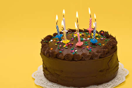 sweetest: Birthday or anniversary cake with lit candles - yellow background - copy space on left. Stock Photo