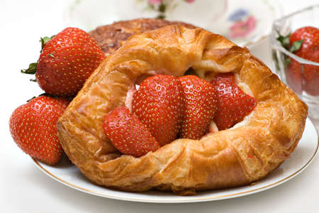 Variety of pastries featuring a strawberry danish - fresh strawberries cup saucer visible. photo