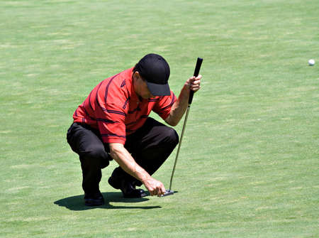 Golfer stoops down to repair the ball mark in the putting green with a golf tee. Stock Photo