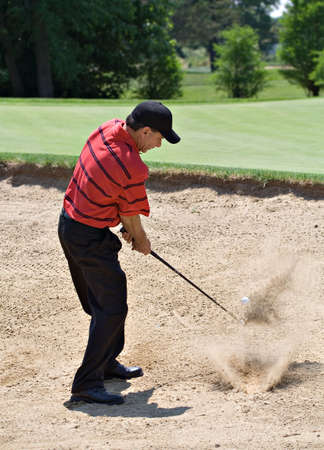 Nicely dressed professional looking male golfer hitting out of sand trap.