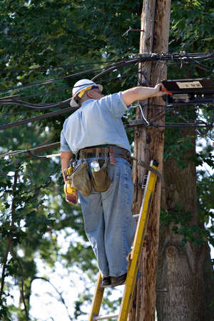 A large sized  repair man works from ladder against utility pole.