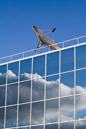 reflect: A business building topped with a satellite dish.  Glass windows reflect sky clouds.