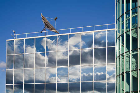 windows: Large satellite dish on top of a large office building with reflective glass windows. Stock Photo