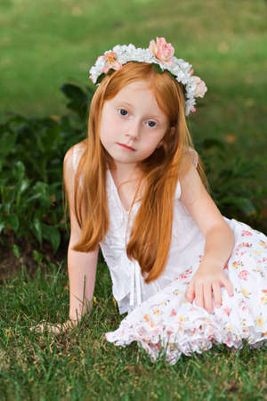 Young red haired girl in garden.