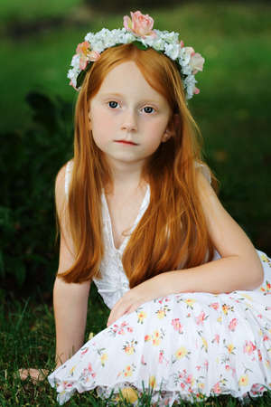 Beautiful girl with long red hair sitting in garden - vintage look.  Banco de Imagens