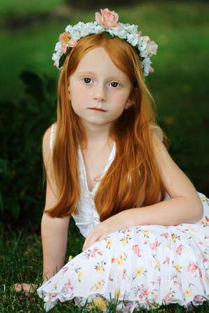 vintage look: Ragazza bella con capelli rossi lunghi che si siedono nel giardino - sguardo dellannata. Archivio Fotografico