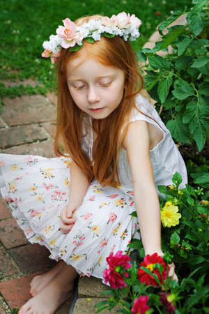 Sweet red-haired girl siting amongst the plants and flowers in garden - vintage feel.  photo