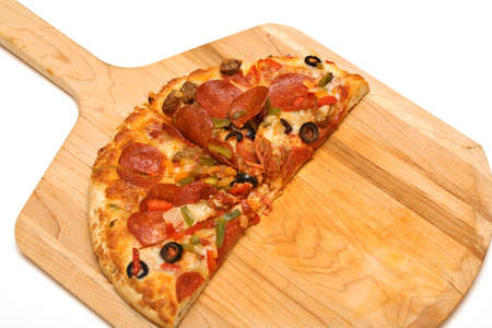 Half of a large pizza on wooden cutting board.