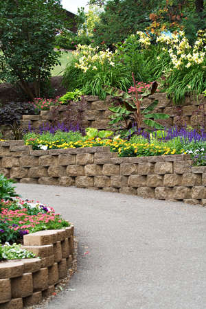 walking path: A walking path flanked by landscaping stones and lush vegetation and flowers.