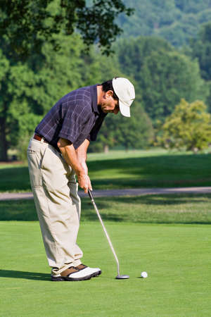 lining up: A male golfer lining up a putt on the golf green. Stock Photo