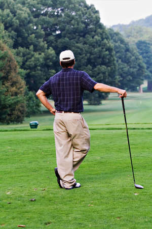 A nicely dressed male golfer waiting for the fairway to clear so that he can make his long drive from the tee.