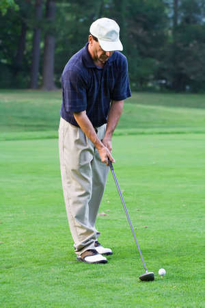 Man teeing  up to hit a big drive onto the fairway.  Imagens