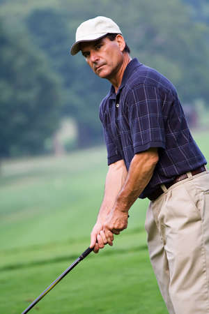 concentrating: A handsome mature man on the golf course - concentrating on his game.  Stock Photo