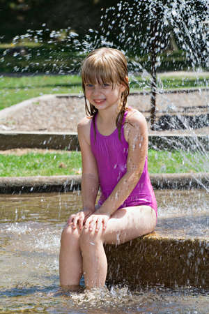 Small blonde girl poses for a photo in water fountain.  photo