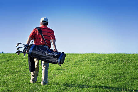 A male golfer walks the golf course - carrying bag of clubs and equipment.  Lomo effect.