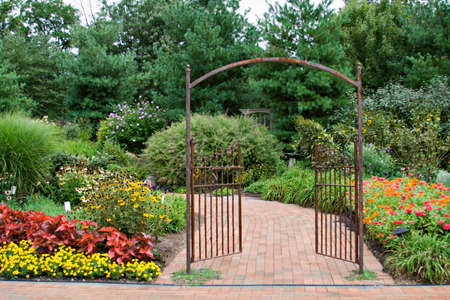 Beautiful floral garden with decorative wrought iron gate.