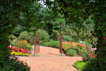 A private flower  garden complete with paths and iron gate - framed by vine covered entrance.