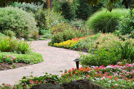 A garden walkway of brick winds through a beautiful garden.