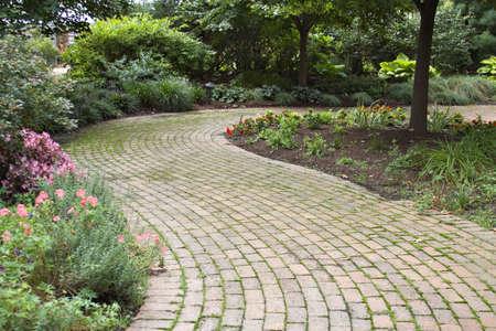 A scenic curving brick walkway through a garden.