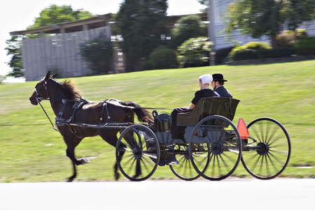 A young Amish couple in Ohio - riding in their horse-drawn  buggy.   Stock Photo