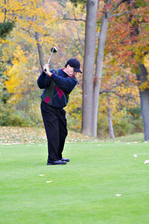 A male golfer plays a game on a beautiful fall day.  photo