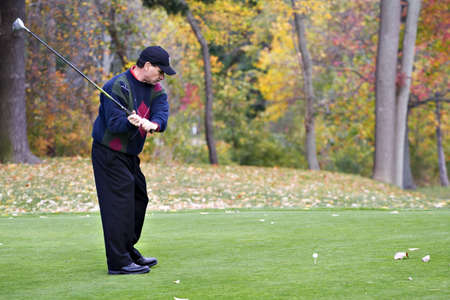 A male golfer playing game on a beautiful fall day  photo