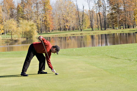 Male Golfer in sweater tees up the ball for a golf shot - Autumn setting photo