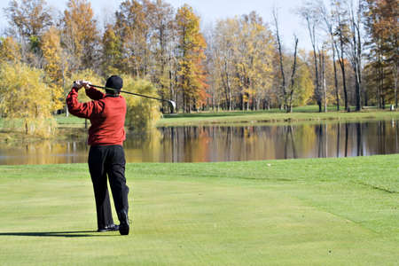 A male golfer smartly dressed in a red sweater is enjoying  a round of November  golf.  photo