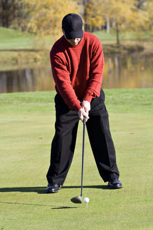 A male golfer smartly dressed in a sweater is enjoying  a round of fall golf.  photo