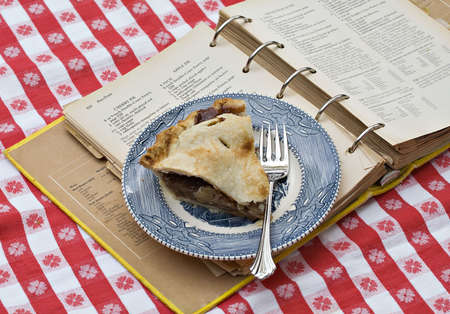 A slice of apple pie on vintage plate resting on top of very old recipe book from which it was made.   Stock Photo